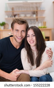 Attractive loving young couple posing together in a close embrace while sitting on a sofa in their living room