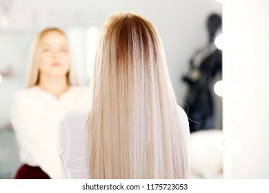 Attractive luxury blonde girl with long hair at the mirror with lamps in the beauty studio.
