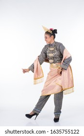 An attractive Malaysian traditional female dancer performing a cultural dance routine called Tarian Zapin in a traditional dance outfit. Full length isolated in white.