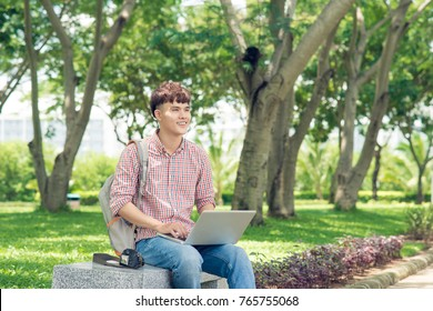 Attractive male asian student is using computer in university's park