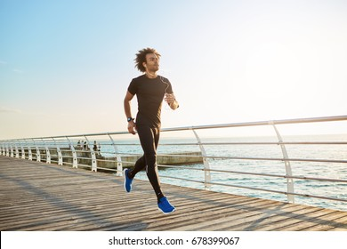 Attractive male athlete wearing stylish black sport clothing and blue sneakers. Figure of man athlete doing cardio running exercises on sunny summer morning. People, sports, fitness and health concept
