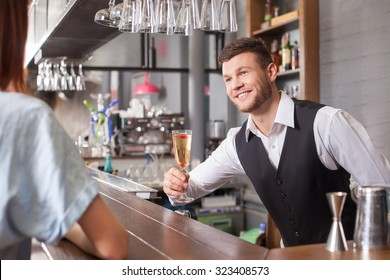 Attractive male bartender is serving woman. He is standing and giving her a cocktail. The man is looking at lady and smiling
