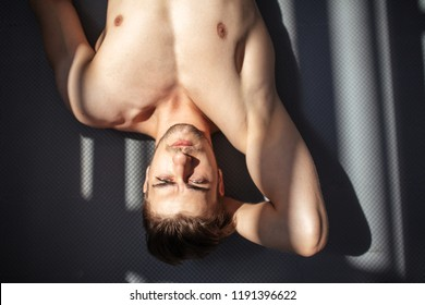 Attractive male bodybuilder lying on the floor indoors in dark gym, sun s rays lighting up his naked torso, showing strong young torso and ripped abs