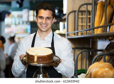 Attractive male confectioner holding delicious cake