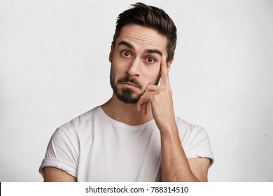 Attractive male with dark beard and mustache looks with wonderment as hears something unexpected, keeps finger on temple, has clever look, isolated over white concrete background. Facial expression