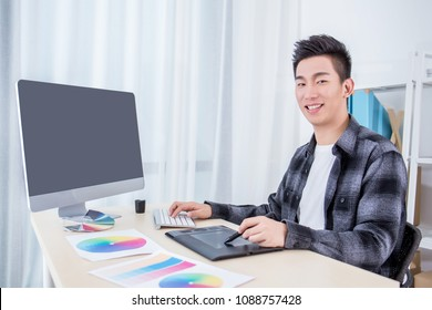 Attractive male designer working in office