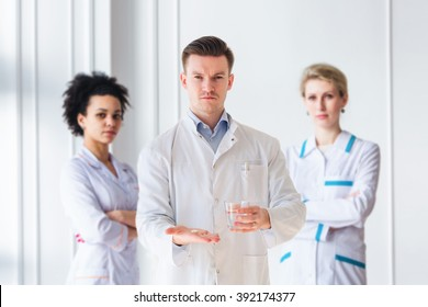 Attractive male doctor giving capsule and glass of water in front of his medical team