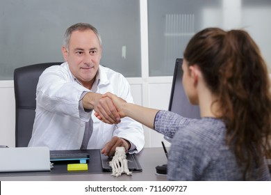 attractive male doctor shaking a patients hands in his office