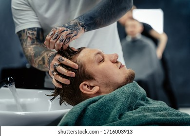 Attractive male is getting a modern haircut in barber shop. Top view of a young man getting his hair washed and his head massaged in a hair salon