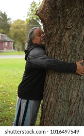 Attractive male with gray hair hugging a tree.