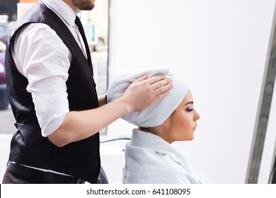 The attractive male master dries the girl's hair with white towel in the beauty salon