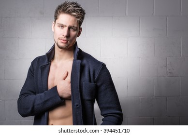 Attractive male model - Handsome young man - Fashionable shirtless hunk wearing a blue jacket, blazer