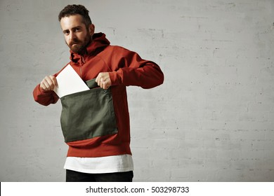 Attractive male model taking a blank white sheet of paper out of the front pocket of his red and gray parka on white background