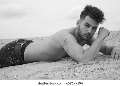 Attractive male model without shirt on the beach