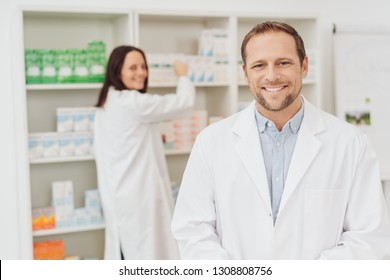 Attractive male pharmacist with a warm friendly smile standing in the foreground in a white lab coat as his female colleague works behind