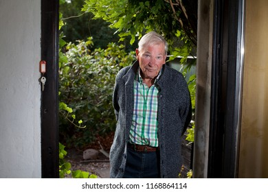 attractive male senior stands in an aopened garden door with vivid green background, he wears a grey cardigan, checkered shirt an blue jeans, his face is attentive and a bit enquiring