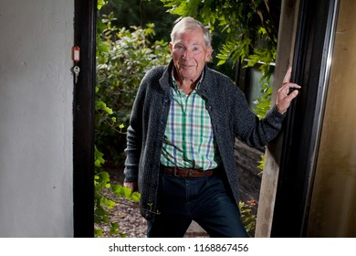 attractive male senior with white hair, blue eyes and leisure wear with cardigan, checkered shirt and blue jeans comes in from the garden, smiles and looks very satisfied