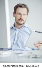 Attractive male sitting at his desk in the office