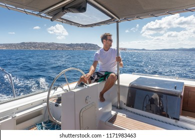 Attractive male skipper navigating the fancy catamaran sailboat on sunny summer day on calm blue sea water. Luxury summer adventure, active nautical vacation.