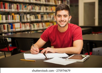 Attractive male university student doing some homework in the school library and smiling