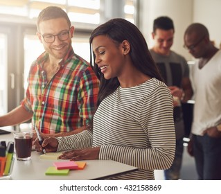 Attractive male wearing eyeglasses and flannel shirt standing next to female co-worker writing on sticky notes at desk with others behind them