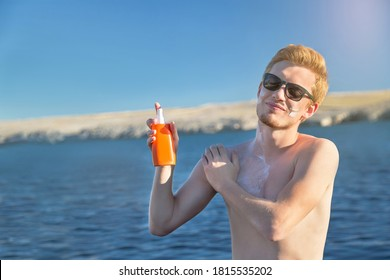 Attractive man applying protective sun cream (solar cream, sunscreen). Young handsome caucasian male model in sunglasses with red hair on the natural background. Outdoor.
