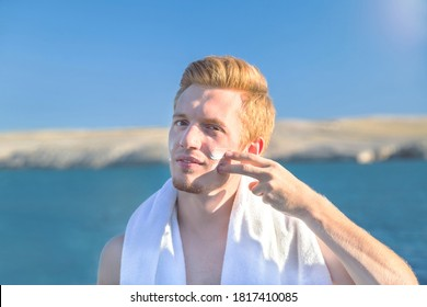 Attractive man applying protective sun cream (solar cream, sunscreen). Young handsome caucasian male model with red hair on the natural background. Outdoor.