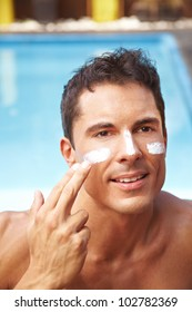 Attractive man applying sunscreen to his face with his finger