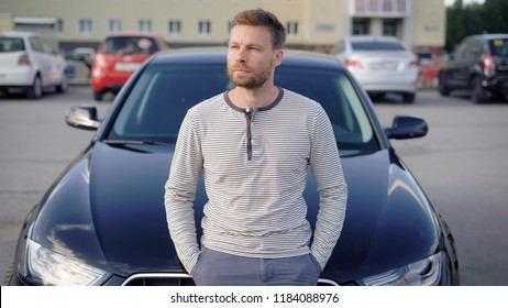An attractive man with a beard stands next to his car in the parking lot. He is thoughtful, and looks away, someone is waiting. Summer day