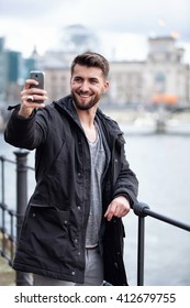 Attractive man with a beard is taking a selfie in front of the Berliner Reichstag