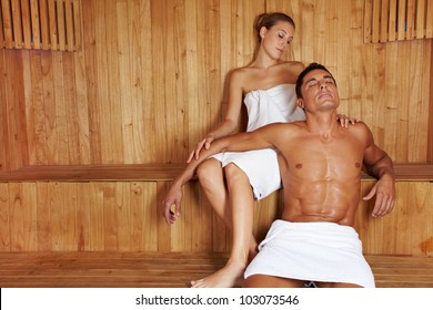 Attractive man and beautiful woman relaxing together in sauna