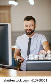 Attractive man with black hair and beard wearing white shirt and tie making coffee, portrait.