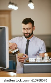 Attractive man with black hair and beard wearing white shirt and tie making coffee, portrait, smiling.