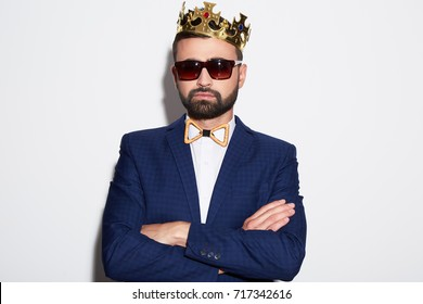 Attractive man with black hair and beard wearing white shirt, suit and sunglasses at white studio background, portrait, copy space, posing, wearing crown.