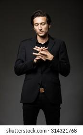 attractive man in black suit on dark background acting