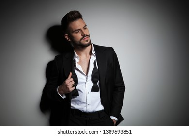 attractive man in black tuxedo adjusting his suit on dramatic background
