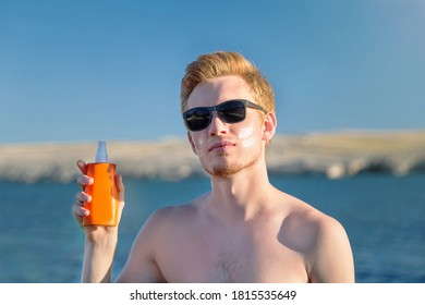 Attractive man with botle of protective sun cream (solar cream, sunscreen ). Young handsome caucasian male model with red hair on the natural background. Outdoor.