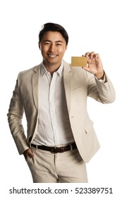 Attractive man in a bright beige suit, holding a golden VIP card smiling towards camera. White background.