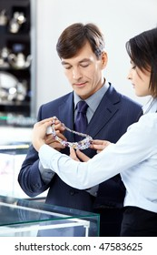 The attractive man chooses a jewel in shop