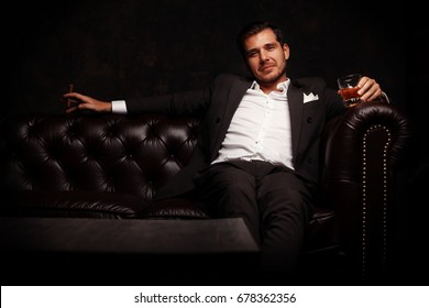 Attractive man with a cigar, and a glass of wine in his hands.