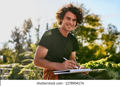 Attractive man with curly hair smiling and writting some notices on paper document and preparing for exam, sitting on the city street. Freelancer businessman looking at the camera makes plans for day