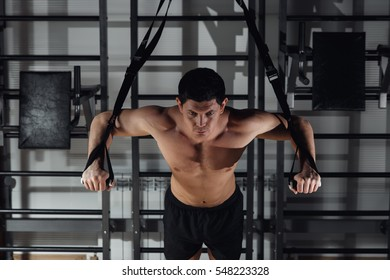 Attractive Man Does Crossfit Push Ups With Fitness Straps In The Gym's Studio