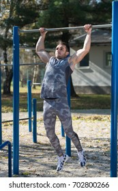 Attractive Man Doing Exercise With Dips Bar in City Park Area - Training and Exercising for Endurance - Healthy Lifestyle Concept Outdoor