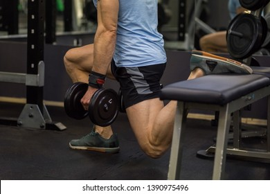 Attractive man doing lunges step-ups with heavy dumbbell.