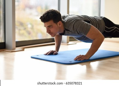 Attractive man doing pushups in the gym on blue mat. Guy wearing sportwears clothes.