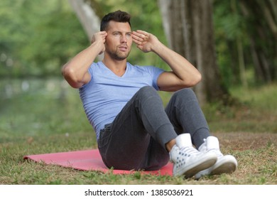 attractive man is doing situps in the fresh grass