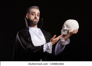 Attractive man in Dracula costume and vampire theet holding a human skull. Man in halloween costume. Man in monster costume.