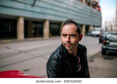 Attractive man dressed in black is sitting on the hood of a car