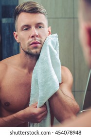Attractive man drying his face in the mirror