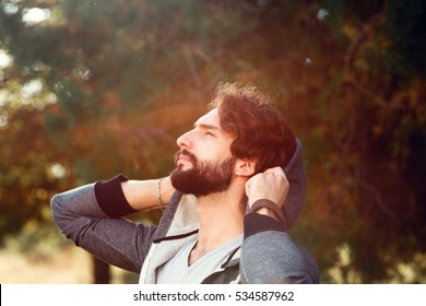 Attractive man enjoying sun warm, close-up. Portrait of young bearded guy, having sunbath in forest. Nature, spring, relax, pleasure concept